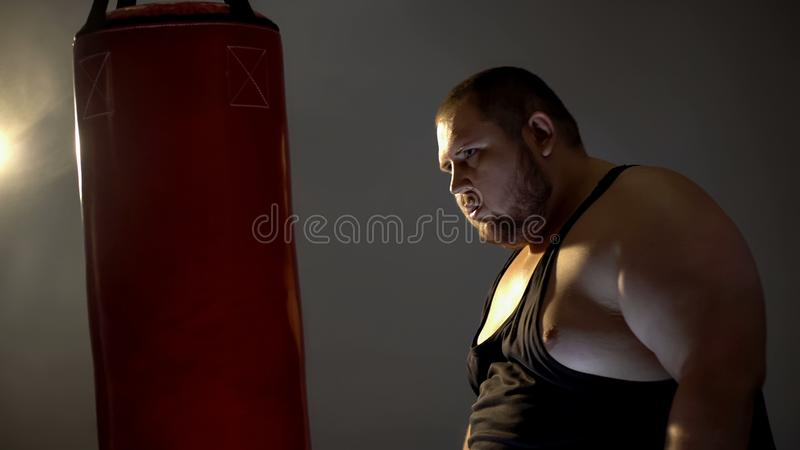 Obese man with aggression looking at punching bag imaging his opponent, box. Stock photo royalty free stock images