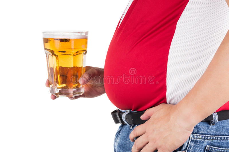 Obese man with big belly holding a glass of refreshing cold beer royalty free stock photos