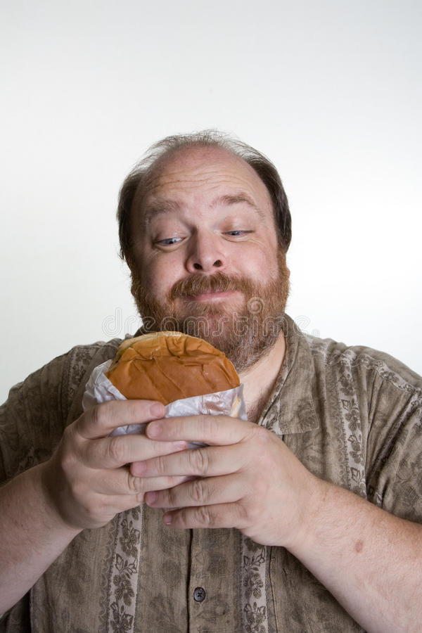 Obese man eating fast food. Overweight man in mid forties eating fast food stock photography