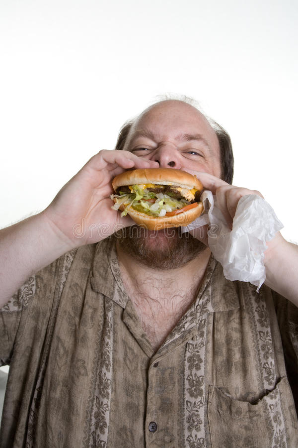Obese man eating fast food. Overweight man in mid forties eating fast food royalty free stock photos