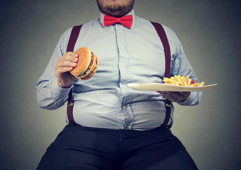 Obese man eating fast food. Crop shot of big man in formal clothes sitting and consuming plate with fast food on gray stock images
