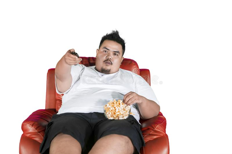 Obese man eats popcorn during watch television. Image of an obese man eating popcorn on the sofa while watching television in the studio stock images