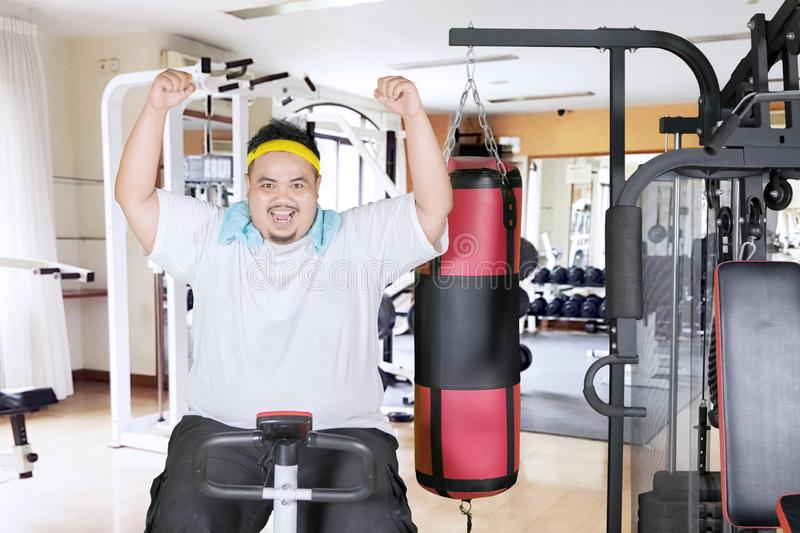 Obese man expresses happy on an exercise bike. Picture of an obese man expressing happiness while using an exercise bike in the gym center royalty free stock photos