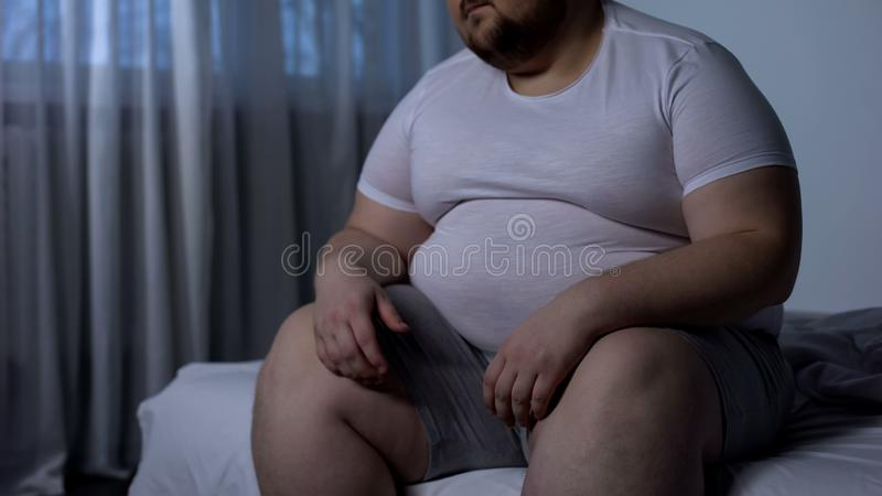 Obese man feels heaviness and pain in stomach, abdominal bloating, indigestion. Stock photo stock photos