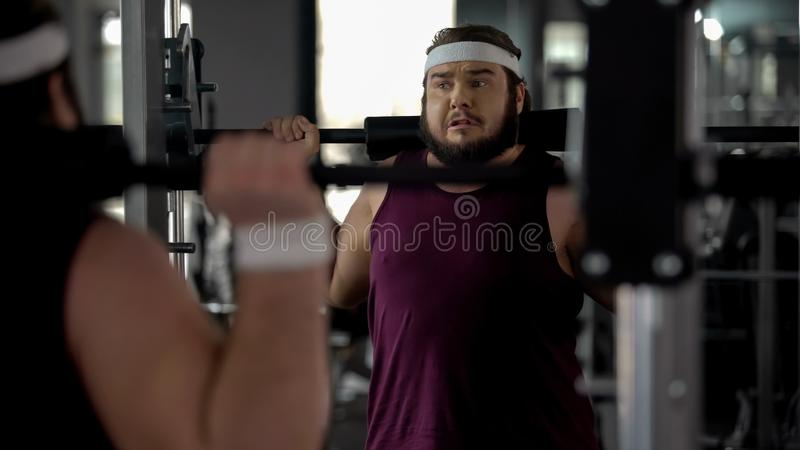 Obese man hardly doing exercise with barbell in gym, fitness workout, sport stock image