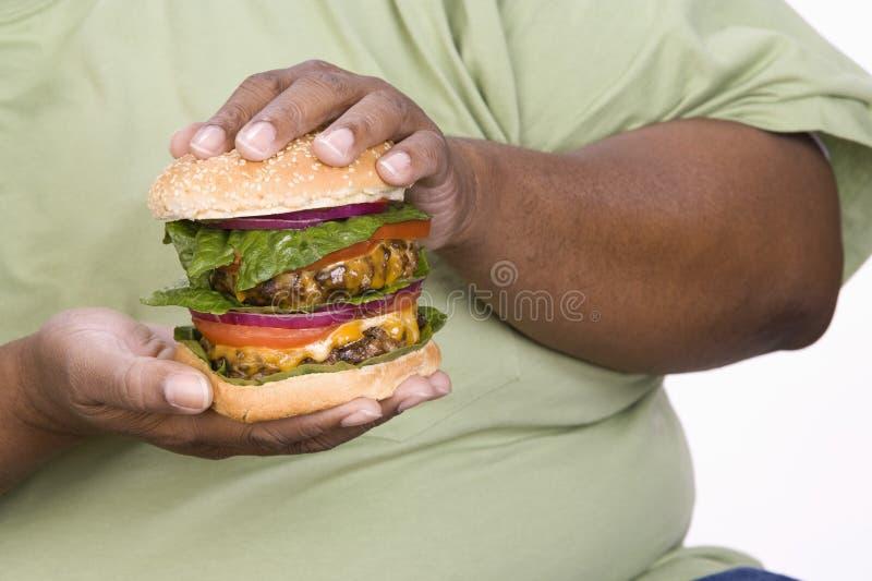 An Obese Man Holding Hamburger royalty free stock photography