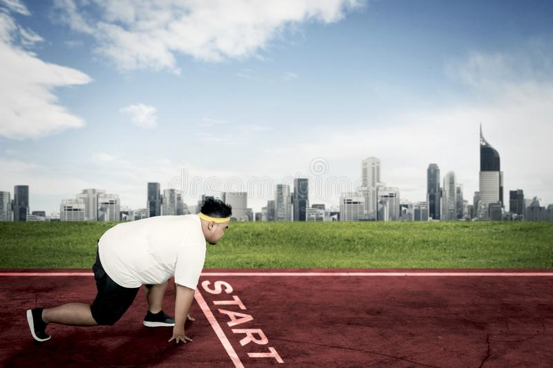 Obese man kneeling on the start line. Side view of an obese man ready to run while kneeling on the start line. Shot at outdoors stock images
