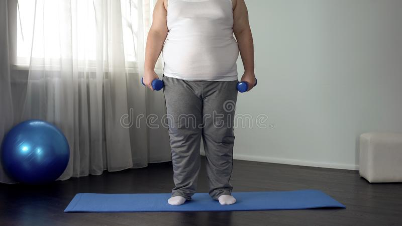 Obese man lifting dumbbells on mat at home, desire to lose weight, fitness. Stock photo stock image