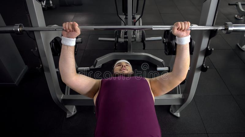 Obese man lifting up barbell, personal gym workout plan, desire to be strong stock photo