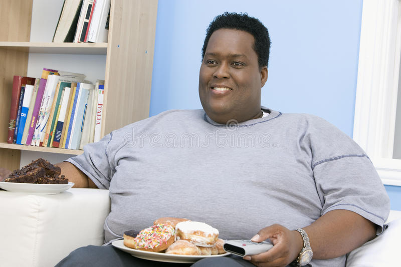 Obese Man Sitting On Sofa stock photos