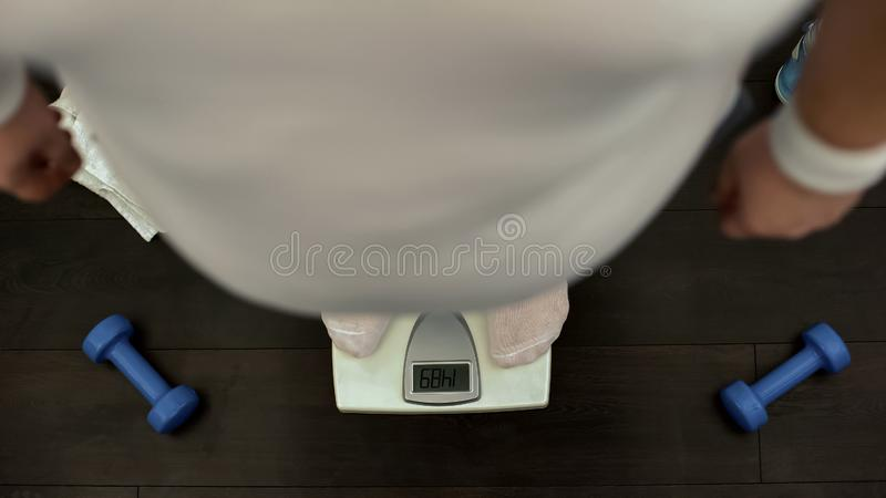 Obese man standing on gym scale, checking weight, slimming training, dieting stock photography