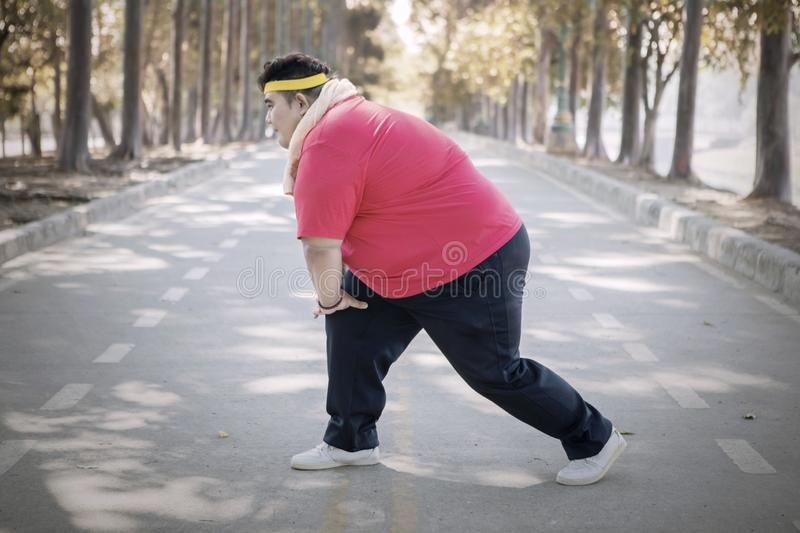 Obese man stretching his leg before exercise stock photography