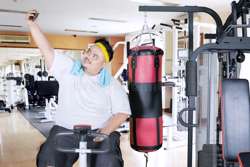 Obese man takes picture on an exercise bike. Picture of obese man using smartphone to take selfie pictures on an exercise bike in the gym center royalty free stock photos