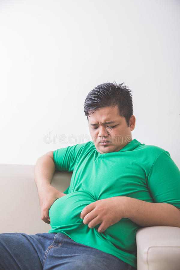 Obese man thinking about his weight problem royalty free stock photography