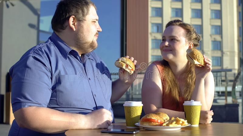 Obese man and woman sharing burgers during romantic date outdoors, calories stock image