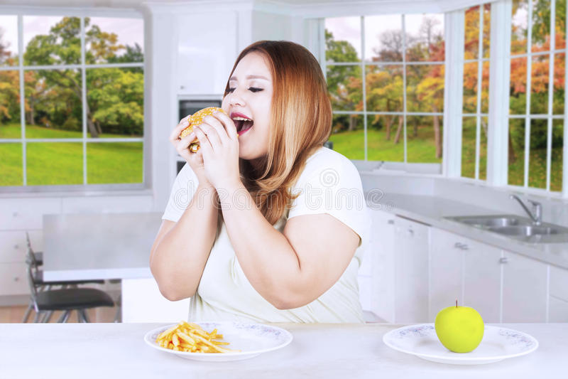 Obese woman choosing to eat junk food. Obese blonde woman ignoring a fresh apple fruit and choosing to eat hamburger at home with autumn background on the window stock photos
