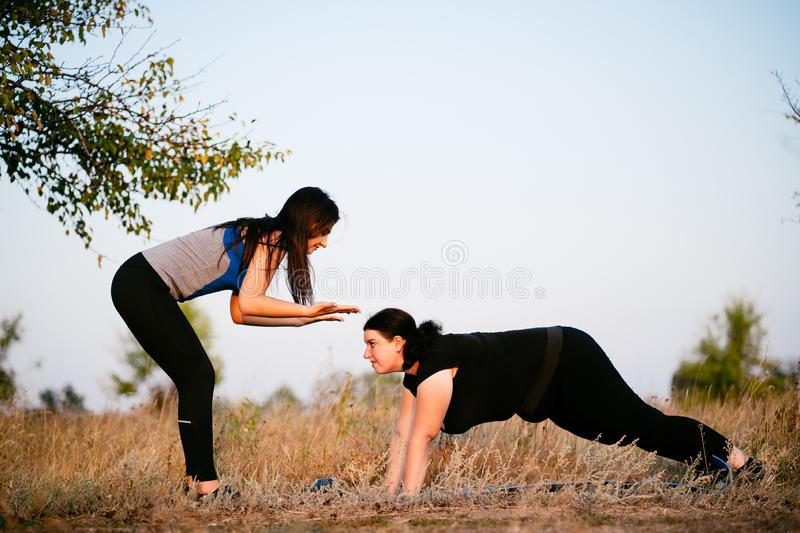 Obese woman doing push-ups with instructor support. Personal trainer working with her client outdoors. Overweight women doing pushups on mat with assistance of royalty free stock photo