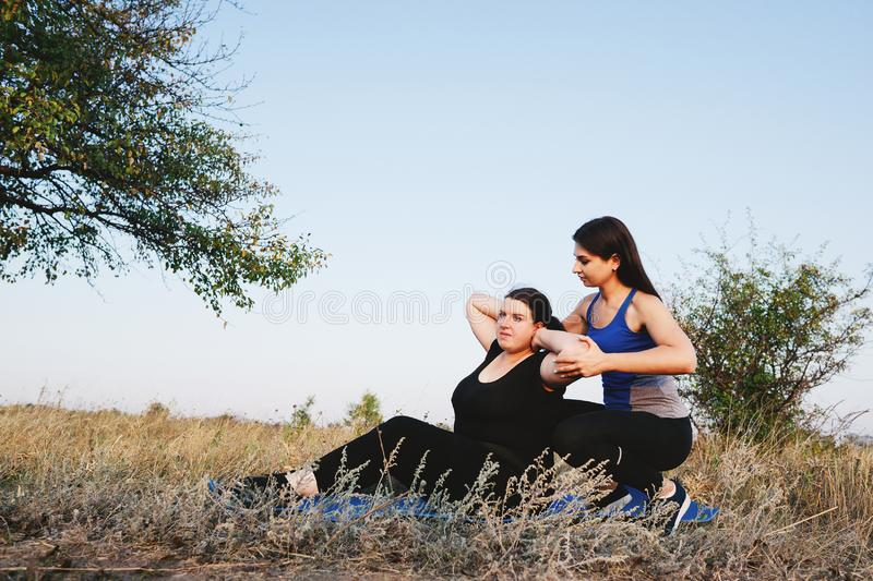Obese woman doing sit-ups with personal trainer. Personal trainer working with her client outdoors. Overweight women doing situps on mat with fitness instructor royalty free stock image