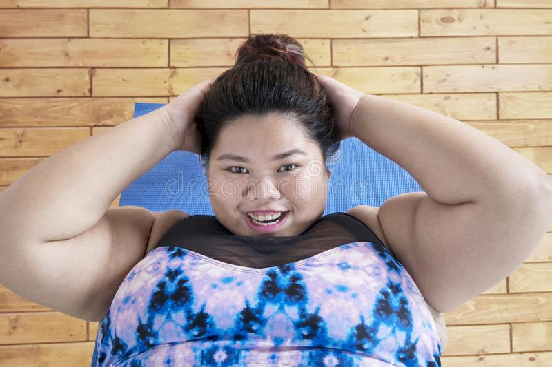 Obese woman doing sit ups. Top view of young obese woman smiling at the camera while doing sit ups over the wooden floor royalty free stock images