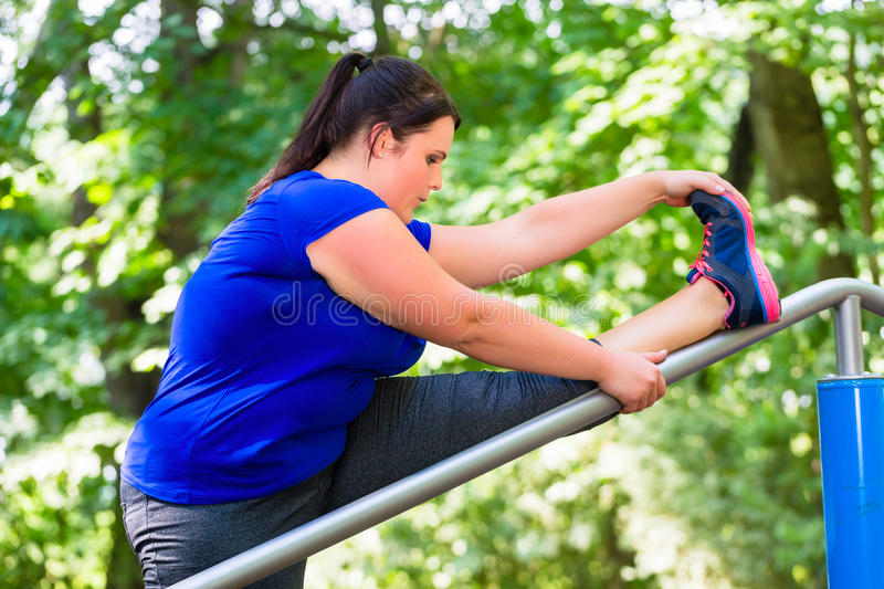 Obese woman doing sport stretching outdoors in park royalty free stock images
