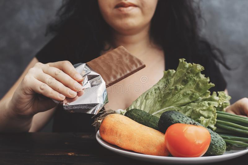 Obese woman eating chocolate refusing healthy food stock images