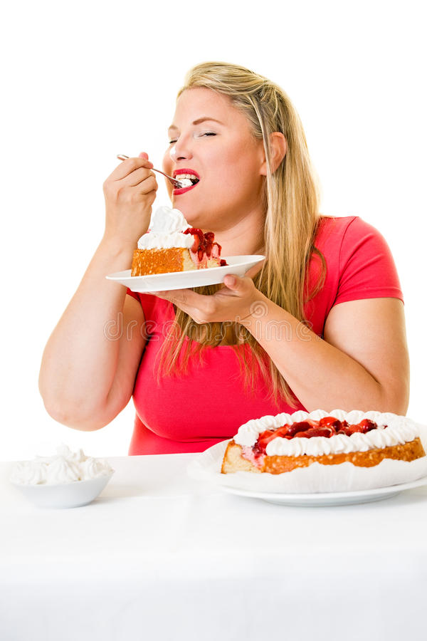 Obese woman eating strawberry cream cakes. Obese young woman eating strawberry cream cakes on white royalty free stock photography