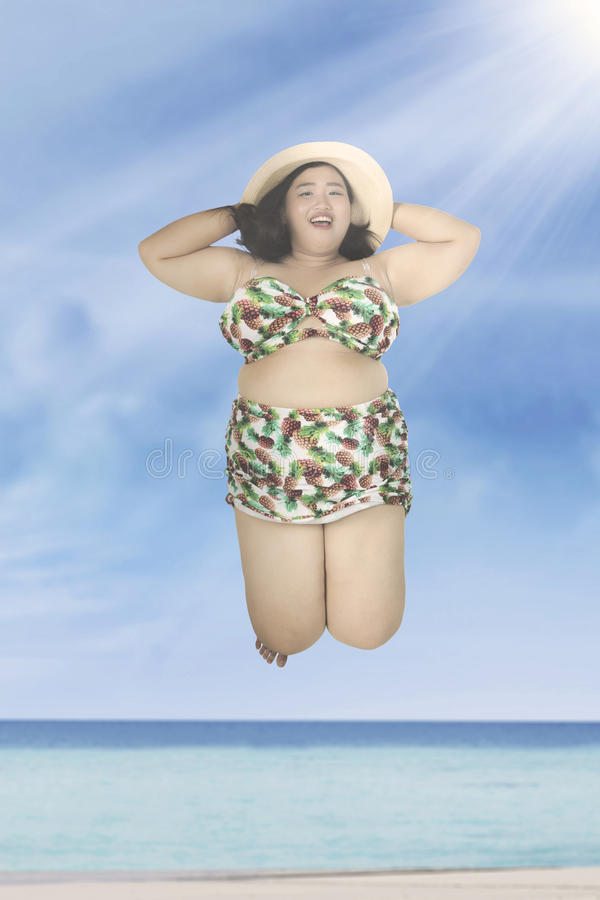Obese woman jumping on beach stock images