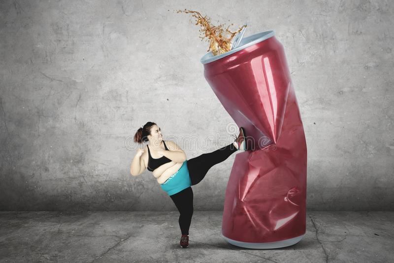 Obese woman kicking soft drink stock photography