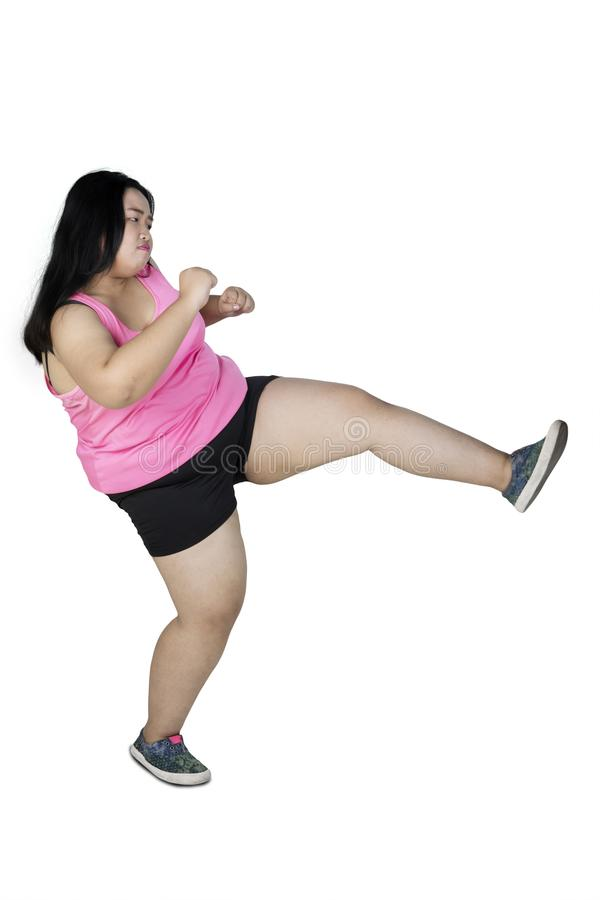 Obese woman kicking something on studio. Portrait of young obese woman wearing sportswear while kicking something in the studio, isolated on white background royalty free stock image
