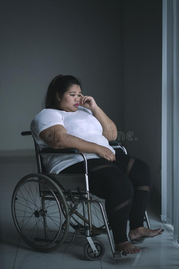 Obese woman looks sad in the wheelchair royalty free stock photography