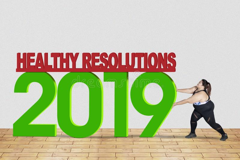 Obese woman pushes text of healthy resolution 2019 royalty free stock photos