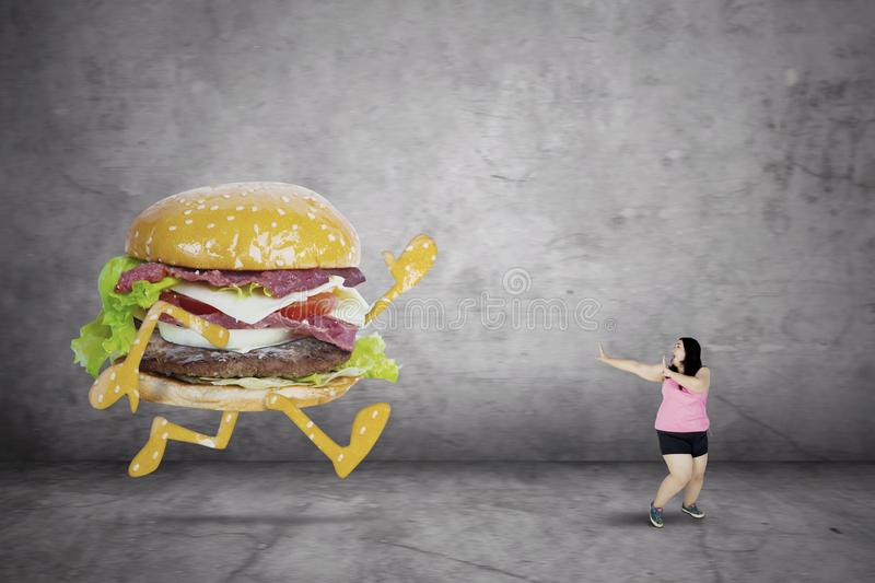 Obese woman running away from a hamburger royalty free stock images