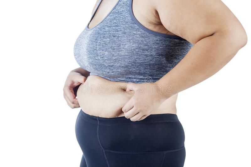 Obese woman squeezing her belly on studio stock image