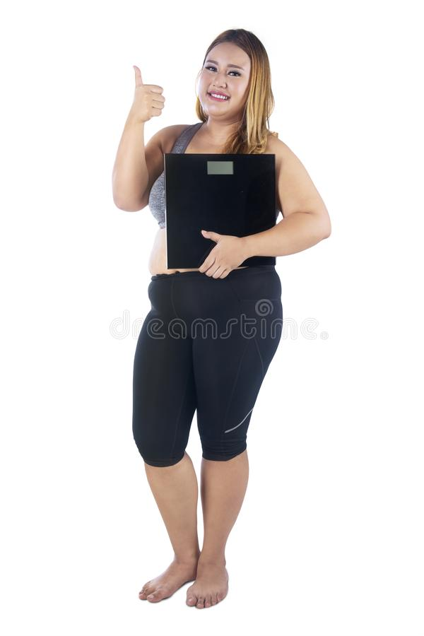 Obese woman with thumb up and weight scales. Portrait of obese woman looks happy while showing her thumb and holding weight scale, isolated on white background stock photos