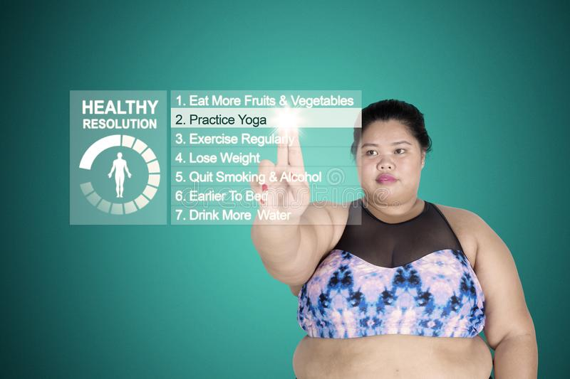 Obese woman touching practice yoga button. Obese woman touching virtual screen while choosing practice yoga button for her healthy resolution royalty free stock images
