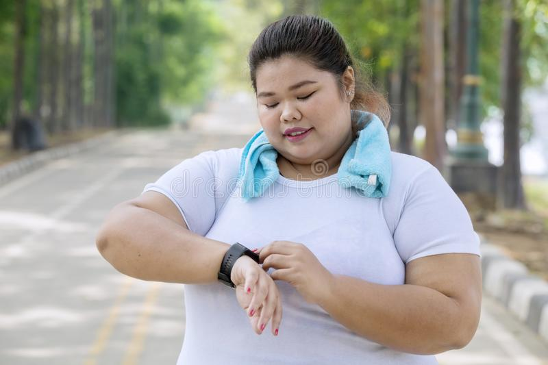 Obese woman wearing her smartwatch on the road royalty free stock photography