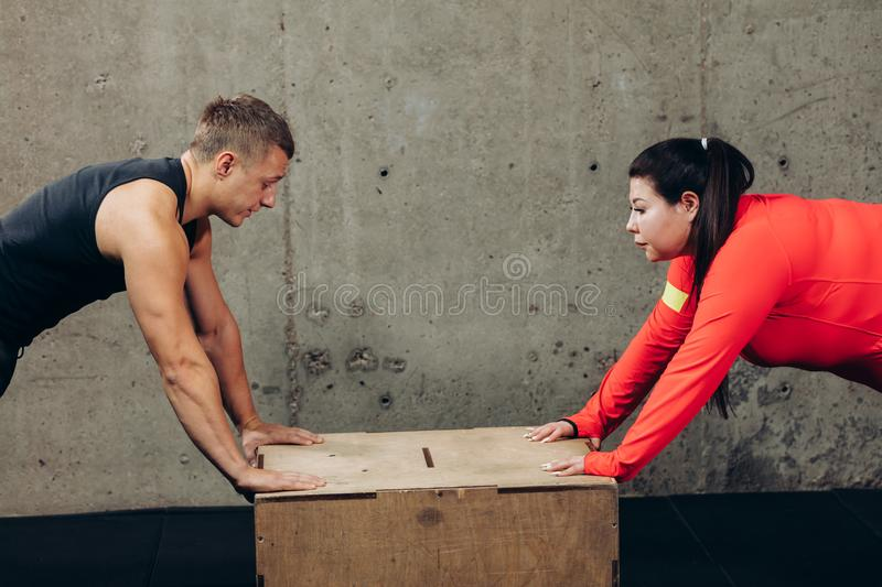 Obese woman and fit man doing push-ups at gym. Obese women and fit men doing push-ups at gym. hobby, interest, free time concept royalty free stock photo