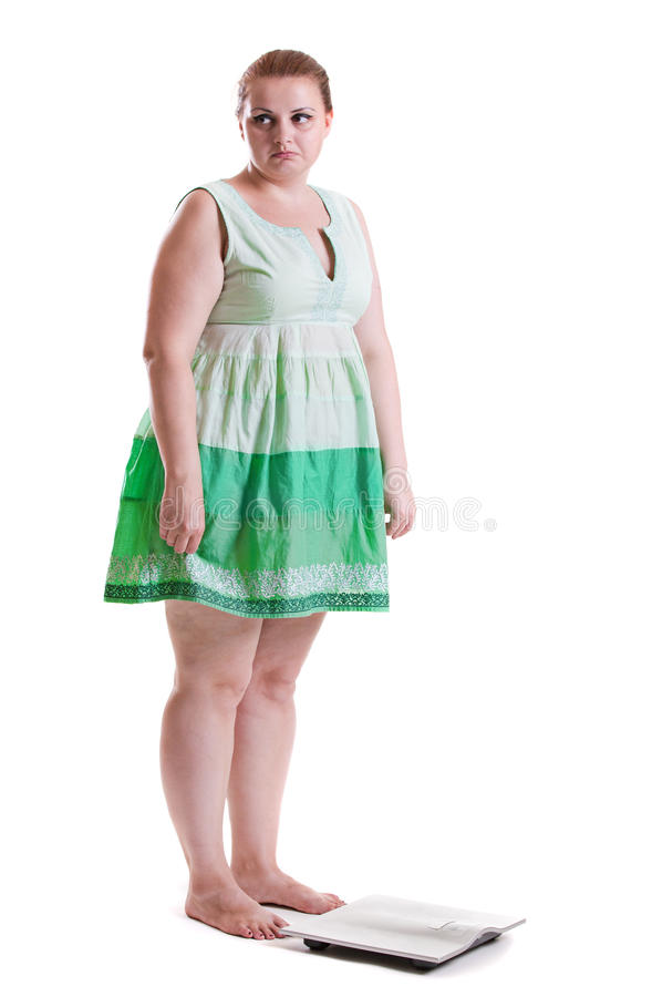 Obese women before weighing. Young white woman with obesity in a dress stands before weighing on floor scales isolated on white background royalty free stock images