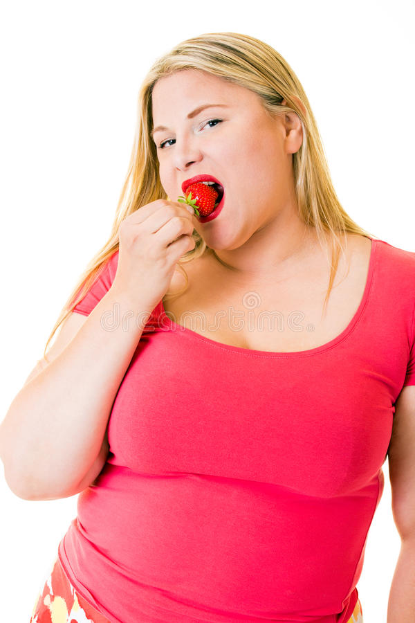 Obese young blond woman eating ripe strawberry stock photos