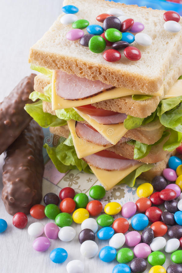Obesity. A concept which illustrate children health issues - an obesity - to big sandwich with some candies royalty free stock photos