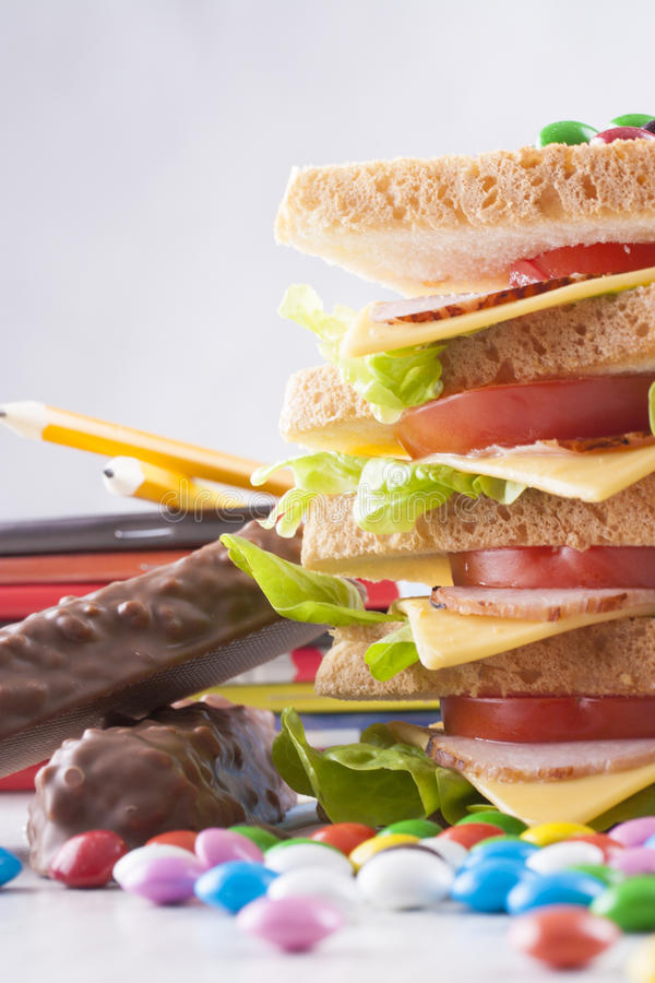 Obesity. A concept which illustrate children health issues - an obesity - to big sandwich with some candies royalty free stock photography