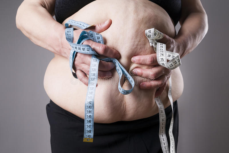 Obesity female body, fat woman with measuring tape stock image
