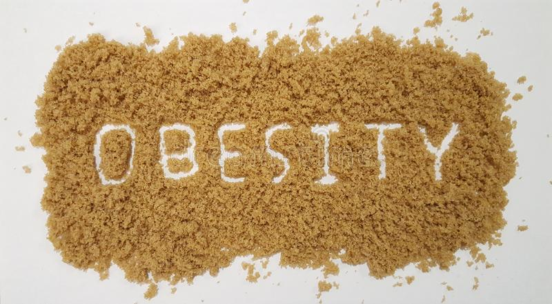 Obesity Spelled Out in Brown Sugar on White Background. Sugar Background stock photography