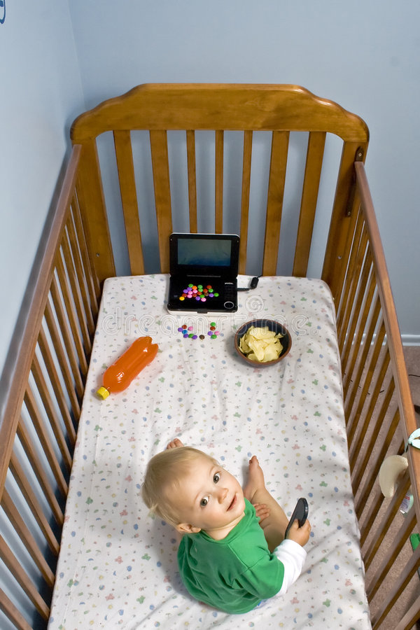 Obesity where does it start. A toddler in crib with junk food. Wounder where obesity starts stock images