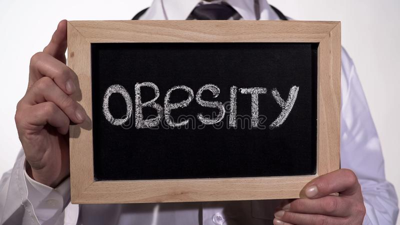 Obesity written on blackboard in doctor hands, healthy nutrition recommendations. Stock footage stock photography