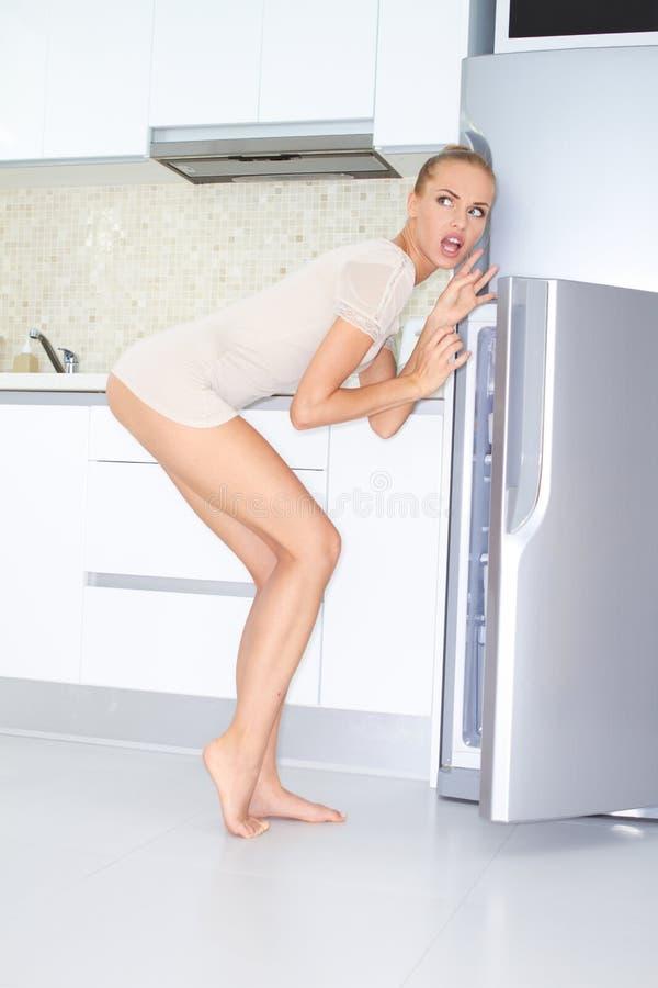 Obeslutsam kvinna som plundrar kylen arkivfoto