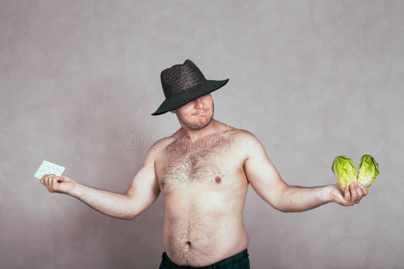 Obeslutsam naken korpulent man med läkemedel och vegetabl arkivfoton