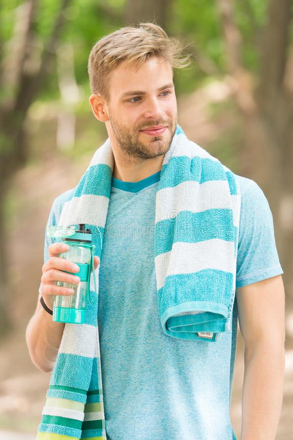 Obey your thirst. Thirsty sportsman. Bearded man holding bottle of drinking water to quench his thirst. Thirst quenching. During sports training or fitness royalty free stock photos