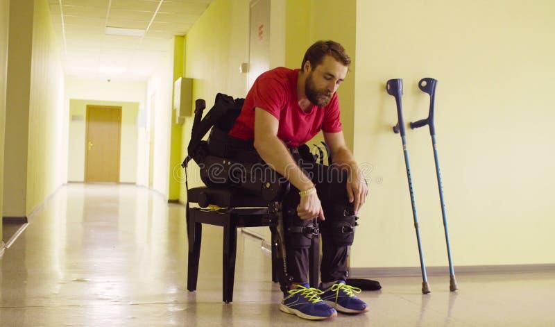 Obezwładnia mężczyzna w mechanicznym exoskeleton obsiadaniu na ławce zdjęcia royalty free
