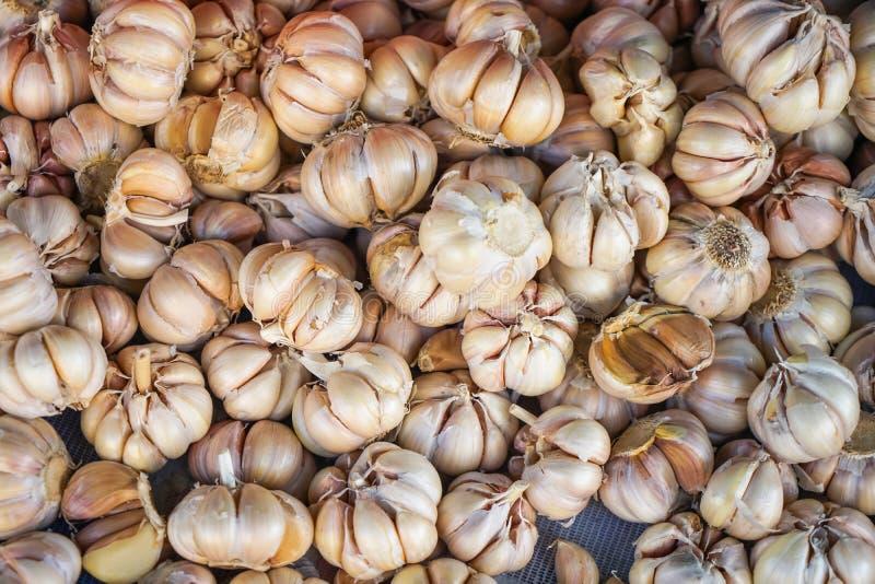 Obfitość stos świeże ziołowe organicznie flavouring czosnku żarówki z cloves tła sprzedawaniem w miejscowym wprowadzać na rynek d obrazy stock